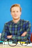 Pair of horn rimmed glasses on a graphic designer's desk. Shallow Depth of Field, focus on the glass