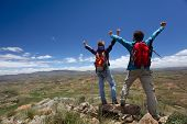 Hikers standing on top of a mountain with raised hands and enjoying valley view