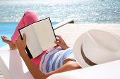image of infinity pool  - Woman reading book relaxed in deck chair - JPG