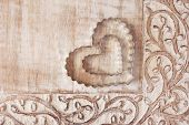 Heart shaped cookie cutters on distressed wood with decorative carved border.