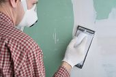 stock photo of respirator  - Contractor sanding the drywall mud using sand trowel - JPG