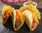 Tacos with ground beef, cheese, vegetables, and guacamole sauce