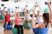 stock photo of senior class  - Instructor Taking Exercise Class At Gym - JPG