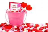 stock photo of valentine candy  - Happy Valentines Day card in a pink pail with candies over white - JPG