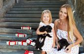 Cute Little Girl And Her Mother Hugging Dog Puppies