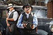 picture of tommy-gun  - Serious mob boss with gun and guard near car