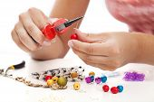 picture of beads  - A person designing colorful earings with plactic beads - JPG