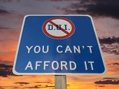DUI you can't afford it warning sign with sunset sky.