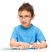 Cute little boy is reading a book while wearing glasses supporting his head with hand, isolated over