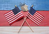 Two crossed American flags on a red, white and blue wood table with military dog tags. Great concept