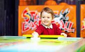stock photo of funfair  - cute happy child playing table air hockey - JPG