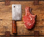 stock photo of red meat  - Raw fresh meat and meat cleaver on wooden background - JPG