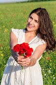 Portrait of beautiful young woman holding poppies bouquet in the field