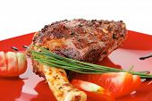 meat over white : grilled meat shoulder on red plate with tomatoes green lettuce isolated on white