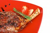meat over white : grlled meat shoulder on red plate with tomatoes green lettuce isolated on white