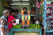 COLOMBO, SRI LANKA - FEBRUARY 22, 2014: Local man buying fruit juice from one of many street vendor