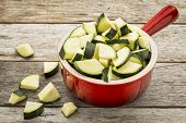 diced and sliced zucchini in red stoneware pot against rustic wooden table