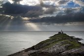 Lighthouse On Headland With Sun Beams Over Ocean Landscape With Long Exposure