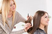 stock photo of hair cutting  - Young beautiful woman having her hair cut at the hairdresser