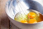 whisking eggs in metal bowl on wooden table