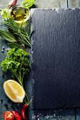 Food background, with herbs, spices, olive oil, salt, lemons and vegetables. Slate and wood backgrou