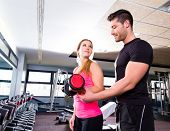 Gym personal trainer man with dumbbell woman fitness weightlifting