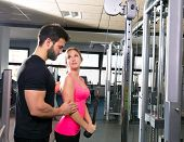 cable pulley system personal trainer man and woman learning at fitness gym