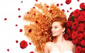 Beauty model girl with long curly red hair and beautiful red roses hairstyle. Fashion woman with Wav