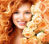 Beauty model girl with long curly red hair and beautiful red roses hairstyle. Fashion woman with Wavy healthy hair. Cute smiling teenage girl. Permed hair