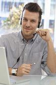 Portrait of happy male dispatcher sitting at desk, using headset.