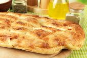 Pita bread on wooden stand with spices on tablecloth close up