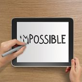 Hand Changing The Word Impossible To Possible With Stylus Eraser On Tablet Computer As Concept