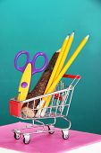 School supplies in supermarket cart on blackboard background