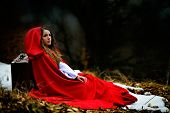 stock photo of cloak  - beautiful woman with red cloak and suitcase alone in the woods - JPG