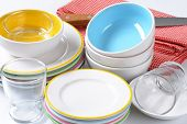 colorful plates and soup bowls with glass, knife and fabric linen
