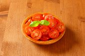 overhead view of portioned cherry tomatoes served in the wooden bowl