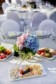 stock photo of banquet  - Elegant banquet tables prepared for a conference or a party and covered with a white tablecloth and decorated with flowers for guests - JPG