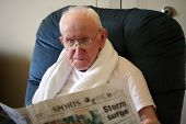 stock photo of fussy  - A elderly man reads the newspaper in his room - JPG