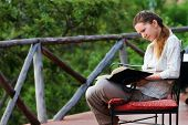 image of breathtaking  - Young woman on safari vacation reading on balcony with breathtaking views of savannah - JPG