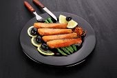 grilled salmon slices with asparagus lemon olives and cutlery on black plate over dark wooden table