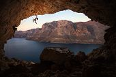 Silhouette of female rock climber on cliff in cave