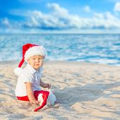 Little Santa boy on the beach.