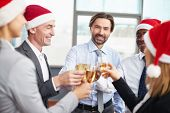Friendly business partners in Santa caps toasting with champagne at corporate party