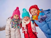 Group of ecstatic children in winterwear having fun outside