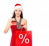 Christmas shopper woman with a credit card isolated on white