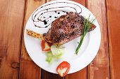 meat on wooden plate : roast shoulder on wood with tomatoes chives and green lettuce on white plate with dark hot sauce