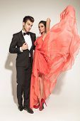 Full body picture of a elegant fashion woman fluttering her coral dress while her lover is fixing his tuxedo,