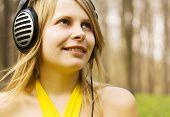 Girl listening music in headphones. Spring nature