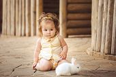 Little girl plays with a rabbit in the village outdoors.