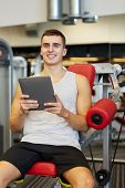 sport, bodybuilding, lifestyle, technology and people concept - smiling young man with tablet pc computer in gym